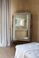 Cheval mirror seen across button-tufted couch in corner of Mediterranean room