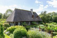 Thatched house in summery cottage garden