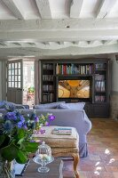 Rustic living room with wood-beamed ceiling and terracotta floor