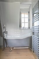 Free-standing bathtub and heated towel rail in farmhouse