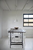 White-painted chars around wooden table on metal trestles in simple dining area
