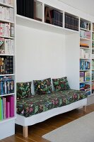 Bench with floral seat cushion and matching scatter cushions integrated in modern fitted shelving