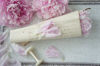 Rolled letter covered in old-fashioned handwriting and filled with peonies