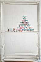 Advent calender hand-made from decorated tin cans in white-painted wooden frame