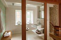 Washstand with shelves in modern bathroom seen through open glass door