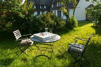 Two chairs and round table in sunny garden