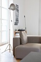 Industrial lamp next to grey sofa in urban loft apartment