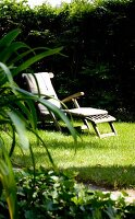 Wooden lounger on lawn in summery garden
