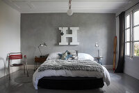 Fur blanket on bed below large white decorative letter on grey stucco lustro wall