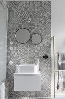 Modern white sink with floating base unit on section of wall with ornate grey tiles