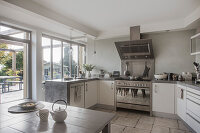 White, U-shaped kitchen counter with concrete worksurface and view of terrace