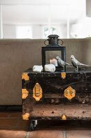 Metal birds, stones and lantern on vintage-style trunk with castors and metal fittings
