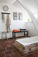 White wood-panelled walls and ceiling in rustic bathroom with brick surround around sunken bathtub