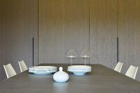 White sugar bowl, stacked plates and two wine glasses on dining table in front of fitted cupboards