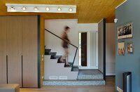 Woman walking down staircase into living area with fitted cupboards and open doorway