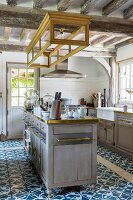 Island counter and ornate blue and white floor tiles in country-house kitchen