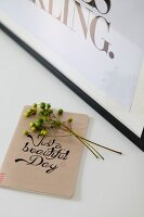 Sprig of berries on top of notebook with calligraphy motto on front