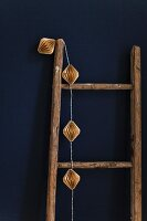 Fairy lights hung on wooden ladder against blue wall