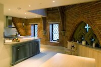 Kitchen with modern installations and Gothic window in converted church