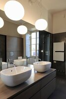 Twin sinks on washstand below large mirror and spherical lamps in bathroom