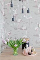 Pendant lamps, tulips and cosmetics in front of flamingo-patterned wallpaper