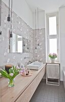 Long washstand and flamingo-patterned wallpaper in bathroom