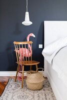 Flamingo behind Windsor chair used as bedside table against dark wall