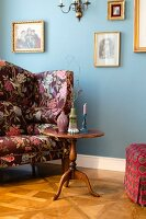Biedermeier table next to floral armchair and blue wall