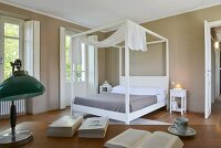 White four-poster bed with canopy in elegant bedroom with dark walls