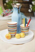 Stripped cups, a Thermos flask and yellow plums on a white tray
