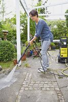 A woman cleaning a terrace with a high pressure cleaner