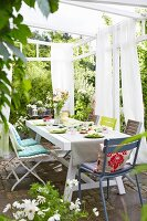 A table laid on a terrace with chairs with coloured cushions under a pergola with light curtains on a white frame