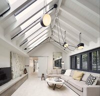 Elongated living room with exposed beams under roof ridge