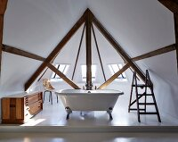 Free-standing bathtub in window bay in attic interior with exposed beams