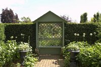 Small arbour with diagonal trellis and tall box hedges bordering summer garden
