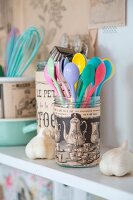 Glass jars covered in vintage printed paper for storing kitchen utensils