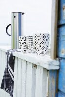 Mugs with black and white graphic patterns on balustrade