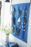 Sewing utensils in wall-mounted organiser made from old jeans pockets
