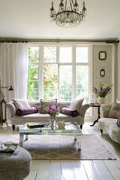 Classic upholstered furniture, mirrored coffee table and lattice windows in elegant living room