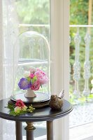 Small vase of flowers under antique glass cover