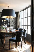 Exotic-wood table and upholstered chairs below hand-crafted pendant lamp in elegant dining room