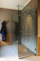 Double shower with modern glass screen and wooden floor in bathroom with traditional wainscoting and tiled floor