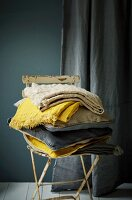 Stack of cushions and cloths in shades of blue and yellow on old garden chair