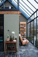 Glass house with stone floor and retro furniture