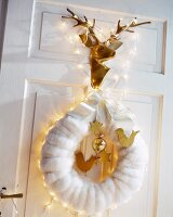 Festive arrangement of white wreath, fairy lights and shiny gold stag's head on door