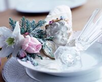 Place setting festively decorated with artificial flowers, cherub and Champagne glass