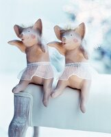 Two angel-pig ornaments arranged on white upholstered chair