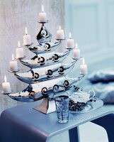 Lit white pillar candles on elegant candle holder shaped like a tree