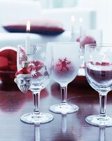 Lit candle in candle holder on edge of etched wine glass and Christmas tree bauble