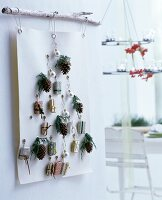 Advent calendar made from white felt with punched eyelets and small wrapped gifts hung from branch